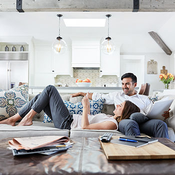 Young Couple relaxing on sofa in living room looking at mobile phone together after work